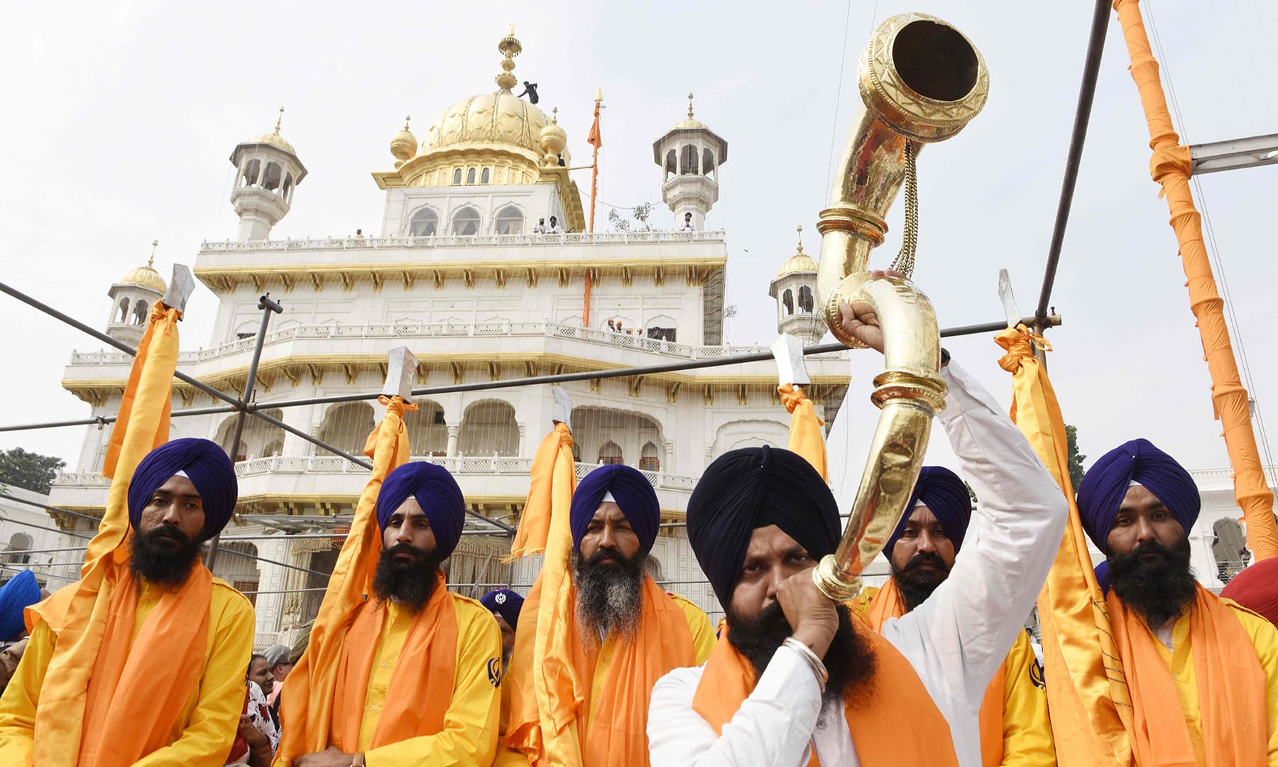 "TOPSHOT - A Sikh devotee plays a musical instrument (C) along with Sikh holy men known as 'Panj Pyare' as they hold Sikh religious flags during a ""Nagar Kirtan"" (holy procession) on the eve of the 550th birth anniversary of Sikhism founder Sri Guru Nanak Dev, at the Golden Temple in Amritsar on November 11, 2019. (Photo by NARINDER NANU / AFP) — AFP or licensors"