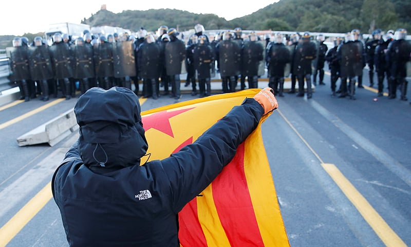 A man holds an Estelada (Catalan separatist flag) in front of French police officers at the AP-7 highway on the French side of the Spanish-French border on November 12, 2019. — Reuters