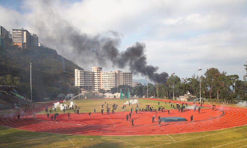 Hong Kong: Students try to clear tear gas canisters from a field during a faceoff with police at Chinese University on Tuesday.—AP