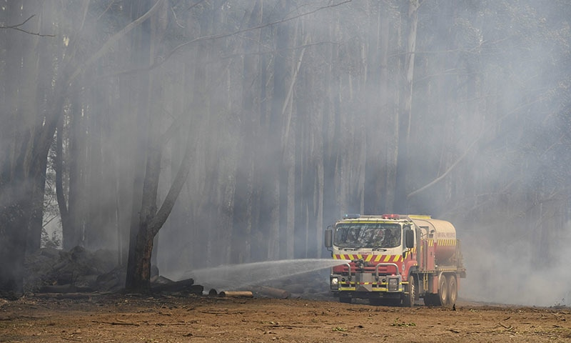 A fire truck hoses down embers after bushfires impacted houses and farmland near the small town of Glenreagh, some 600kms north of Sydney, on November 13. — AFP