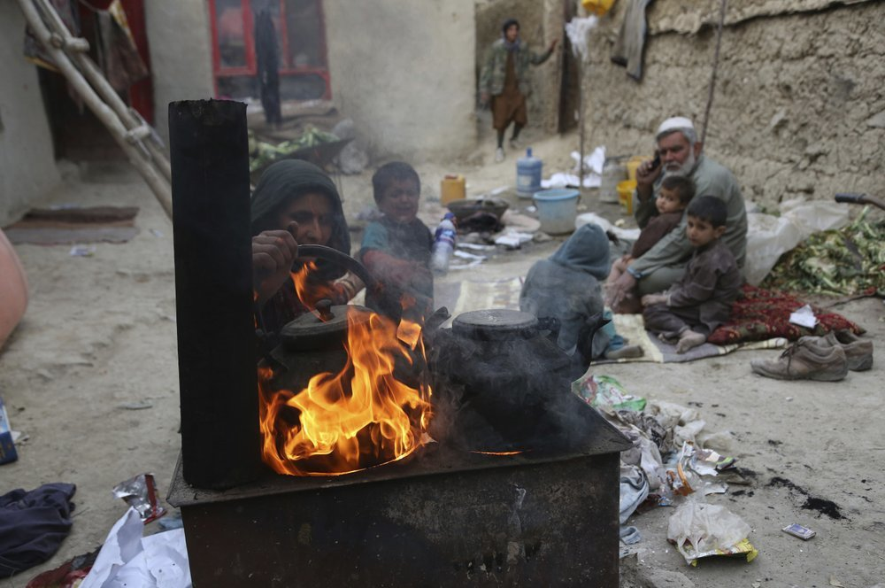 Yousuf, who fled with his family from his home in eastern Afghanistan eight years ago to escape the war, sits with children while his wife burns plastic as she makes tea, in Kabul, Afghanistan. ─ AP