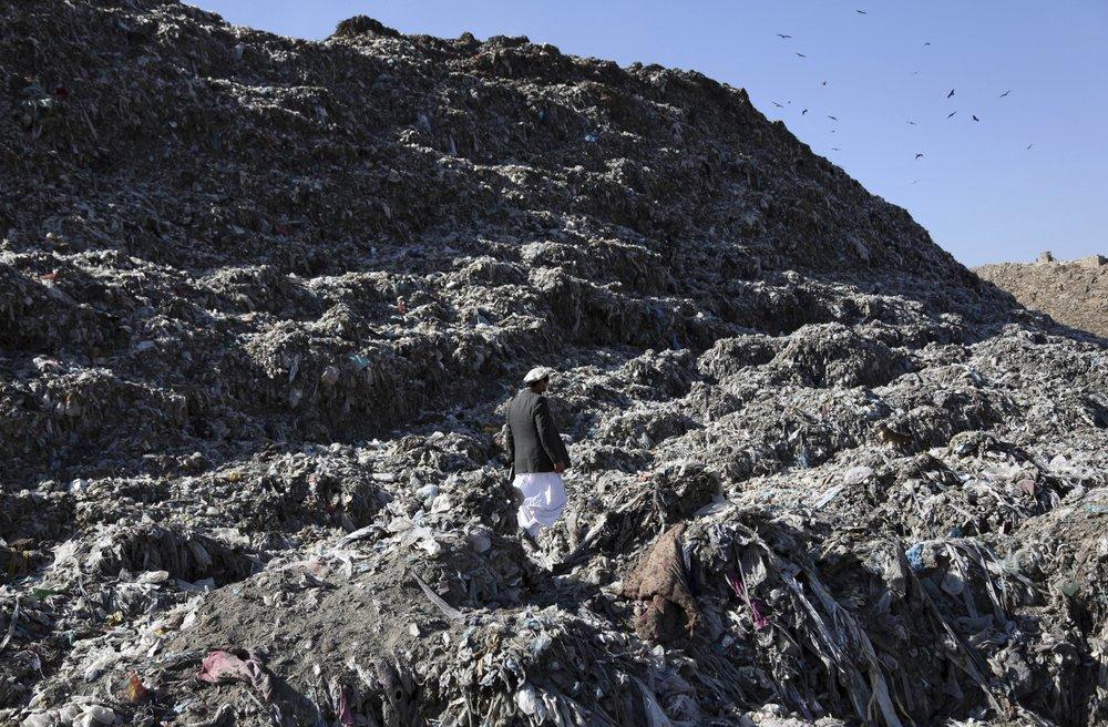 In this Oct 23 photo, Abdul Basir Akhundzada, head of Kabul municipality garbage dump yard, walks at garbage dump yard on the outskirts of Kabul, Afghanistan. ─ AP