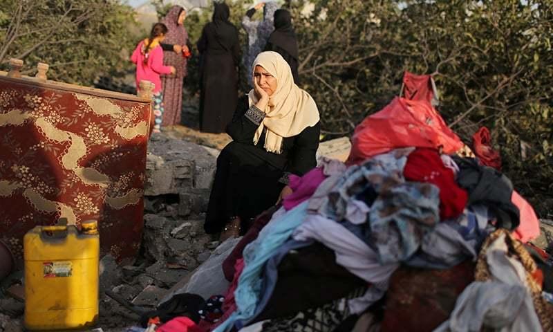 اسرائیل کے فضائی حملوں میں گھر تباہ ہونے پر ایک خاتون افسردہ گھر کے باقیات کو دیکھ رہی ہیں — فوٹو: رائٹرز