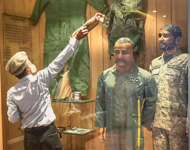 An employee cleans the glass display hosting the likeness of Wing Commander Abhinandan at the PAF Museum on Wednesday.—Fahim Siddiqi / White Star