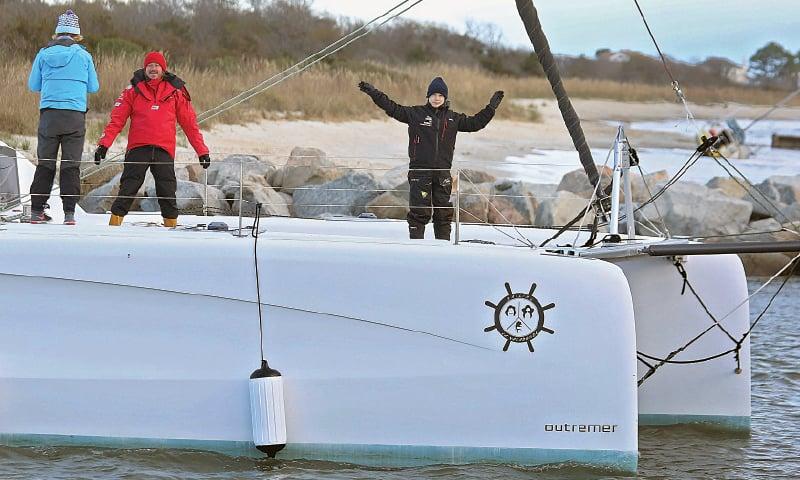 Greta Thunberg waves from catamaran La Vagabonde as it departs Salt Ponds on Wednesday.—AP