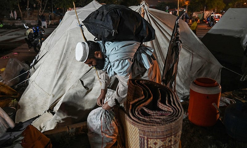 A supporter of JUI-F packs his belongings after the sit-in protest was called off in Islamabad on November 13. — AFP