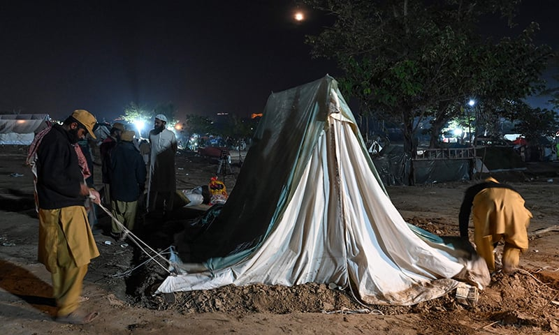 Supporters of JUI-F remove a tent after their sit-in protest was called off in Islamabad on November 13. — AFP