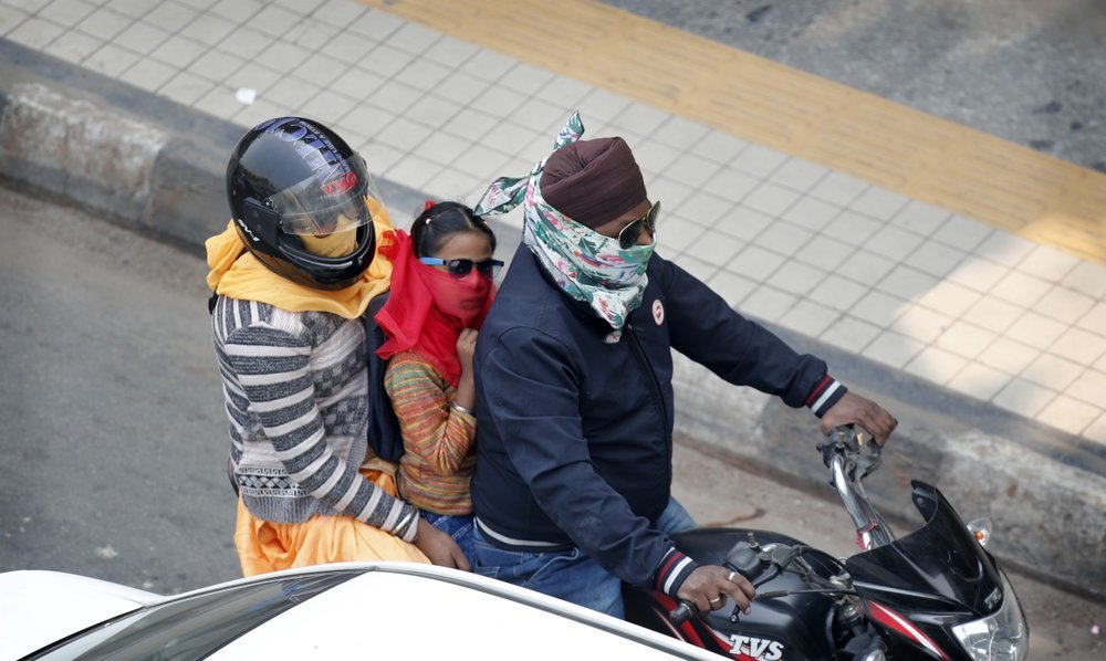 A family covers their face with clothe to save themselves from pollution as they ride on a motorcycle in New Delhi, India, on Tuesday. — AP