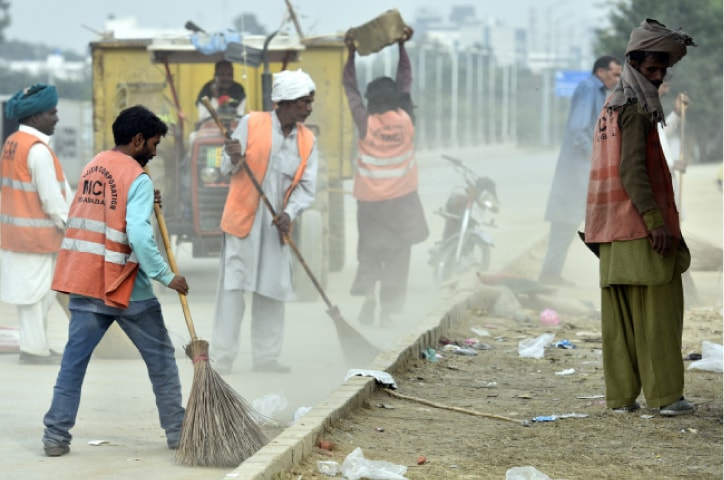 MCI workers collect garbage after protesters leave the sit-in. — Photo by Tanveer Shahzad