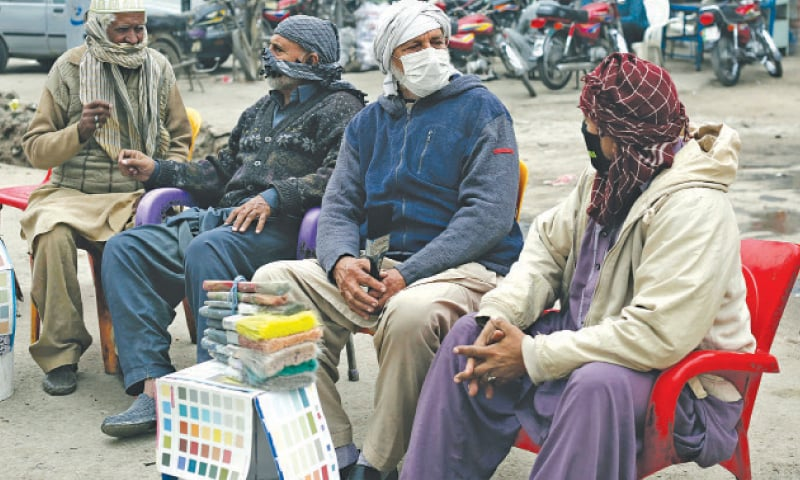 Labourers use masks and cloth to avoid smog on GT Road.  — White Star