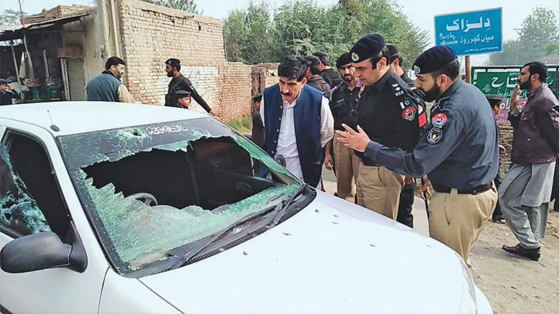 Police officials inspect the car of CTD DSP Ghani Khan after the attack in Mian Gujjar area of Peshawar on Thursday morning. — Dawn