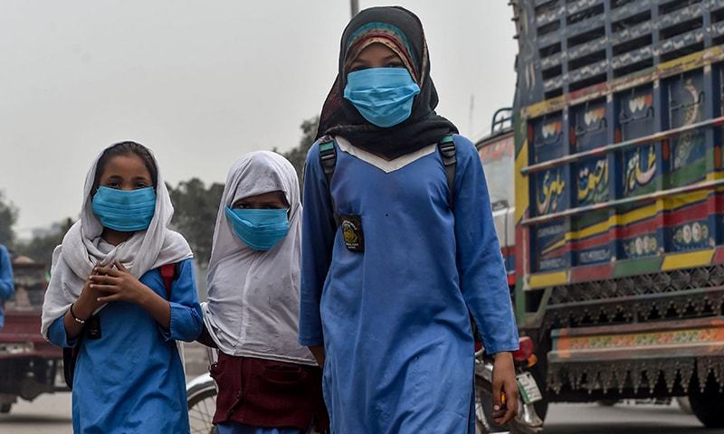 Students wear masks as they go to school amid heavy smog conditions in Lahore on November 14, 2019. — AFP/File