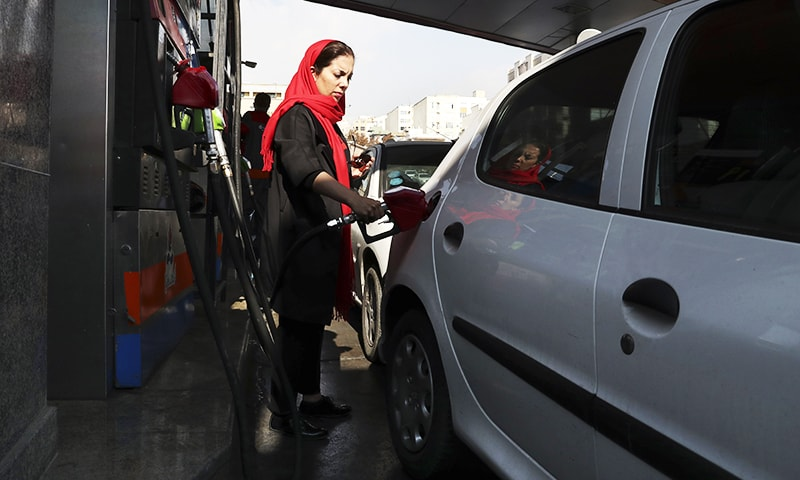 A woman fills her car at a gas station in Tehran Iran Friday
