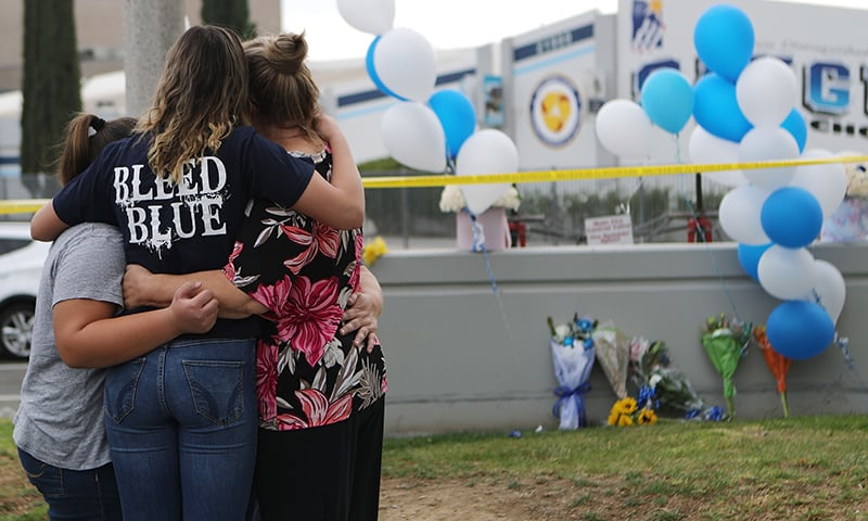 A Saugus High School student (2nd L) is embraced as she visits a makeshift memorial in front of the school for victims of the shooting there on November 15, 2019 in Santa Clarita, California. — AFP