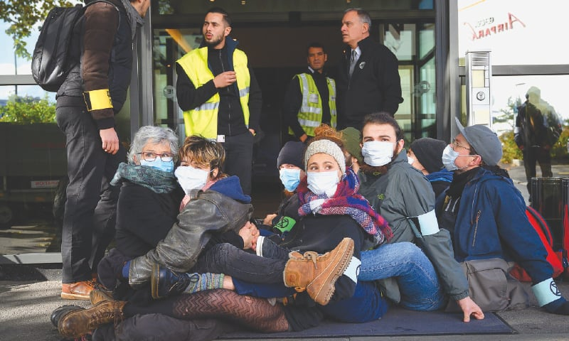 Geneva: Activists seat in front of airport staff members to block an entrance at Geneva airport's private jet terminal, during a protest by the climate change action group Extinction Rebellion (XR) on Saturday.—AFP