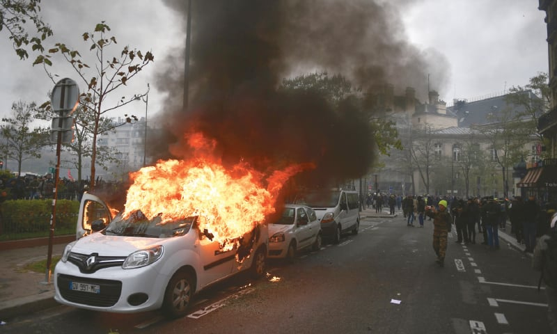 """Paris: Protesters stand near a burning car during a demonstration of the """"yellow vest"""" marking the first anniversary of the movement on Saturday.—AFP"""
