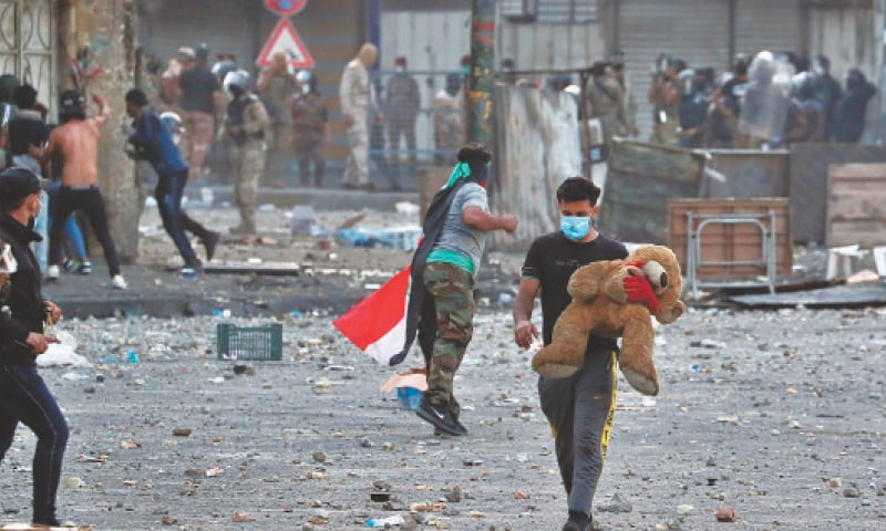 A PROTESTER holds his Teddy Bear during clashes between Iraqi security forces and anti-government demonstrators, at Khilani Square in Baghdad on Friday.—AP