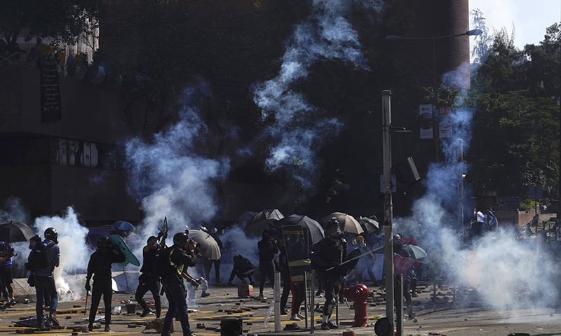 Protestors react as police fire tear gas at Hong Kong Polytechnic University in Hong Kong on Sunday. — AP