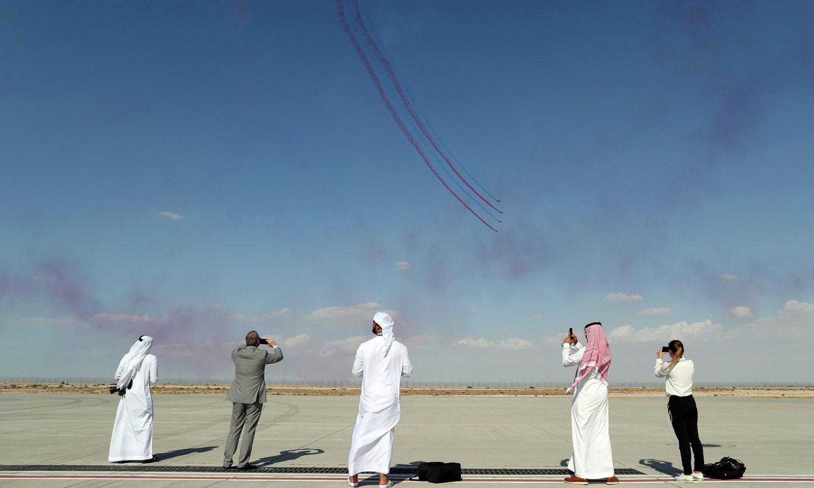آیئر شو میں شرکت کرنے والے فضا میں موجود جہازوں کی تصاویر لے رہے ہیں — فوٹو: رائٹرز