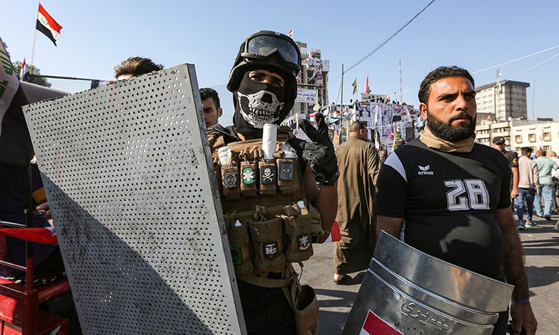 An Iraqi man wearing a balaclava and a helmet fitted with safety goggles flashes the victory gesture while holding an improvised shield as he stands alongside another at the entrance of al-Jumhuriya bridge at the sit-in in the capital Baghdad's Tahrir Square amidst ongoing anti-government demonstrations on November 17. — AFP