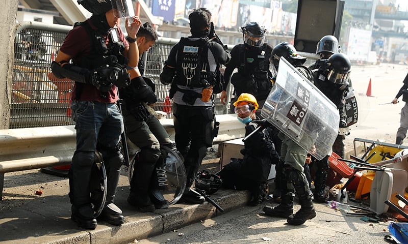 A protester is detained by riot police while attempting to leave the campus of Hong Kong Polytechnic University (PolyU) during clashes with police in Hong Kong, China on November 18. — Reuters