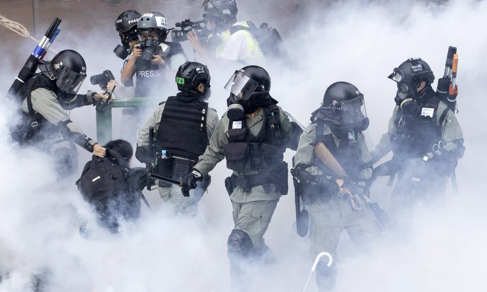 Police in riot gear move through a cloud of smoke as they detain a protester at the Hong Kong Polytechnic University on Monday. — AP