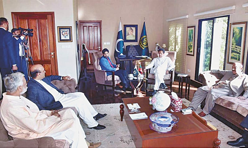 ISLAMABAD: Prime Minister Imran Khan speaks to Pakistan Tehreek-i-Insaf leaders from Narowal district on Monday. The PTI members — Ibrarul Haq, Chaudhry Tariq Anees and retired Col Javed Safdar Kahloon — congratulated the prime minister on Kartarpur Corridor opening and invited him to visit Shakargarh tehsil.—APP