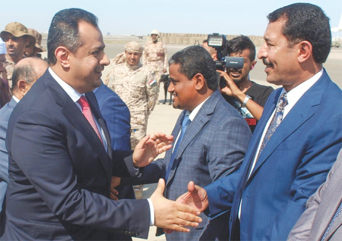 ADEN: Yemen's Prime Minister Maeen Abdulmalik Saeed (left) shakes hands with an official upon arrival here on Monday.—AFP