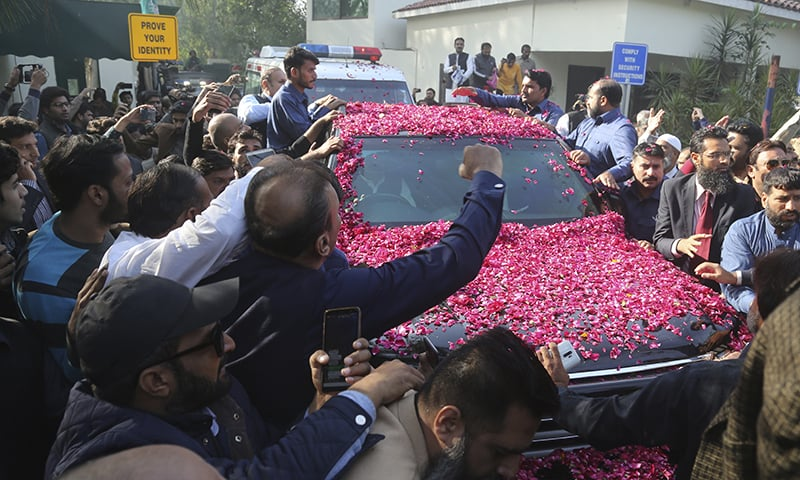 Supporters of ailing former prime minister Nawaz Sharif surround his vehicle at the Lahore airport. — AP