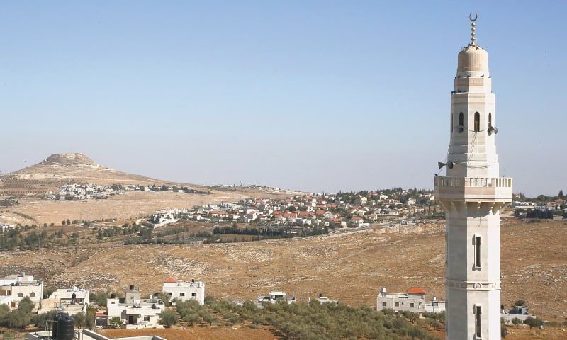 BETHLEHEM: The minaret of a mosque stands on the foreground as the Israeli settlement of Tekoa (centre) is pictured near this  West Bank town.—AFP