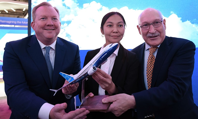 Stanley Deal (L), President and Chief Executing Office at Boeing, poses for a picture with Alma Aliguzhinova (C), Chief Planning Officer at Air Astana, and Anthony Regan (R), Chief Operating Officer at Air Astana, after signing an agreement in Dubai on November 19, 2019. — AFP