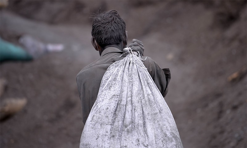 A labourer carries a sack of iron ash at a waste site used by steel factories. — AFP/File