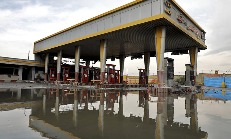 A gas station that was attacked during protests over rises in government-set gasoline prices is reflected in a puddle, in Tehran, Iran on Wednesday. — AP