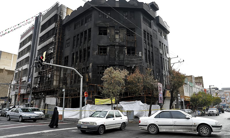 Traffic passes a building that was set ablaze during recent protests over government-set gasoline prices rises, in Tehran, Iran on Wednesday. — AP