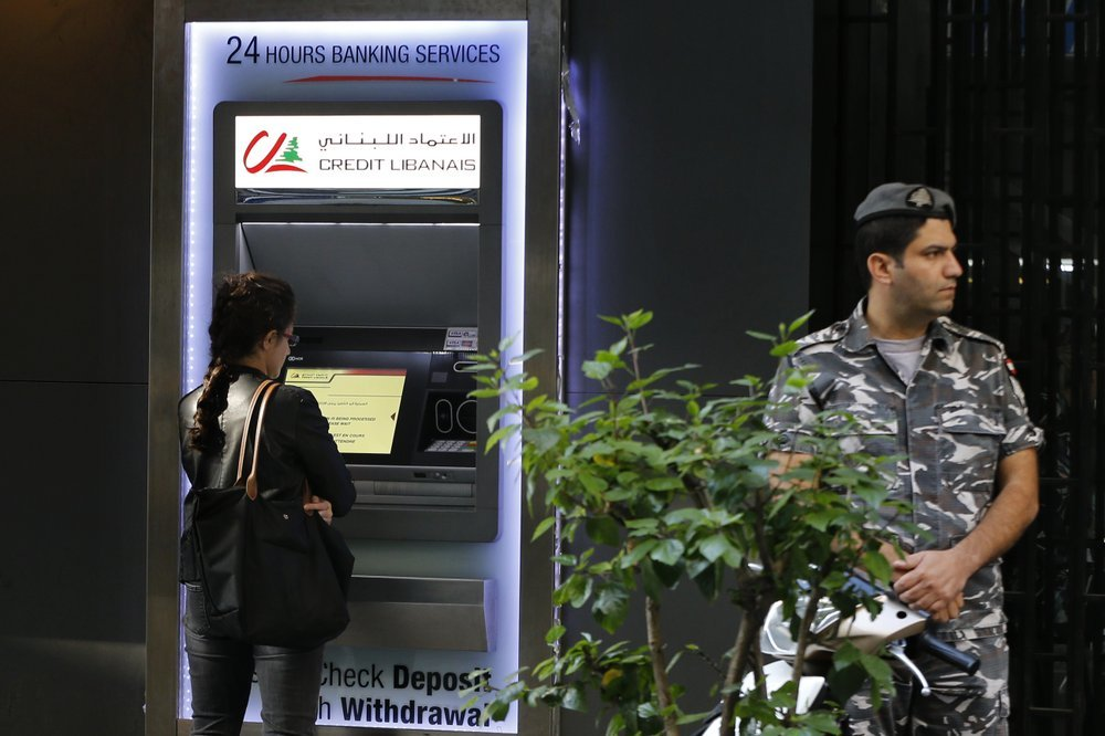 A woman uses ATM outside a bank, as a Lebanese policeman stands guard, in Beirut, Lebanon, on Nov 20. ─ AP