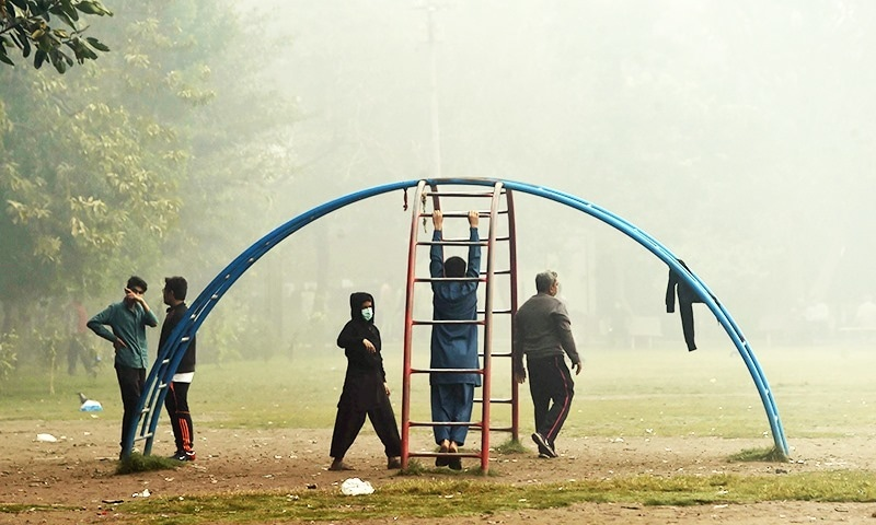 Children play in a park amid heavy smog conditions in Lahore on Thursday. — AFP
