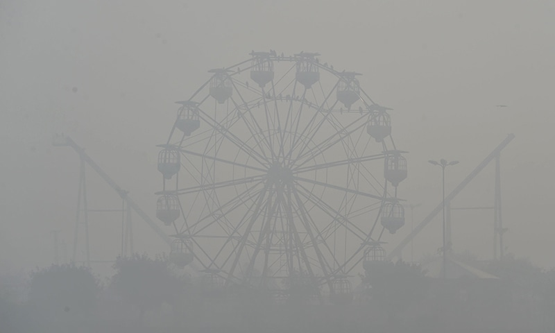 A ferris wheel is seen amid heavy smog conditions in Lahore on Thursday. — AFP