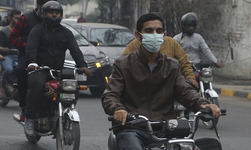 A motorcyclists wears face mask as heavy smog blankets Lahore on Thursday, Nov 21. — AP