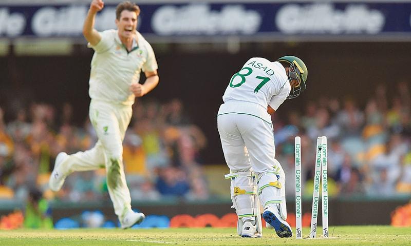 BRISBANE: Australian paceman Pat Cummins celebrates after cleaning up Pakistan batsman Asad Shafiq during the first Test at the Gabba on Thursday.—AFP