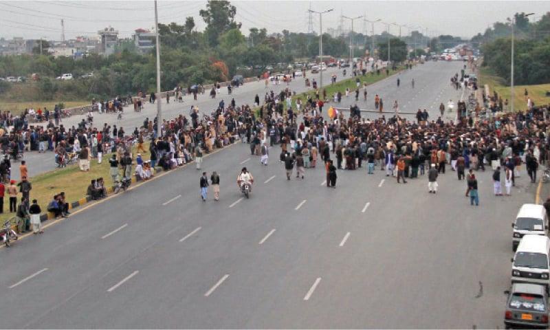Relatives of those killed late Thursday night block Islamabad Expressway near Dhoke Kala Khan on Friday. — Photo by Mohammad Asim