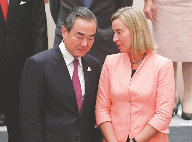 NAGOYA: China's Foreign Minister Wang Yi and EU's foreign policy chief Federica Mogherini exchange views just before a group photograph at the G20 Foreign Ministers' Meeting on Saturday.—Reuters