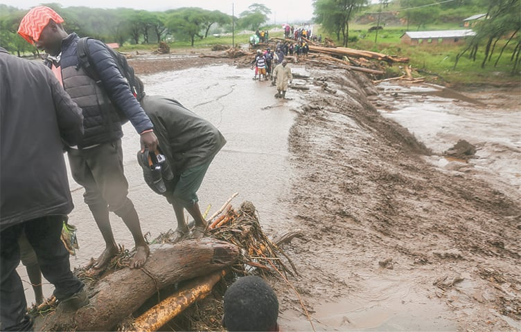 Passengers from stranded vehicles cross floodwaters on foot on the road in western Kenya on Saturday.—AP