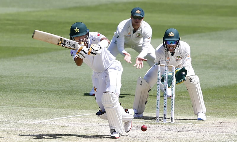 Pakistan's Babar Azam, left, plays a shot as Australia's wicketkeeper Tim Paine, right, looks on during their cricket test match in Brisbane, Australia on Sunday. — AP