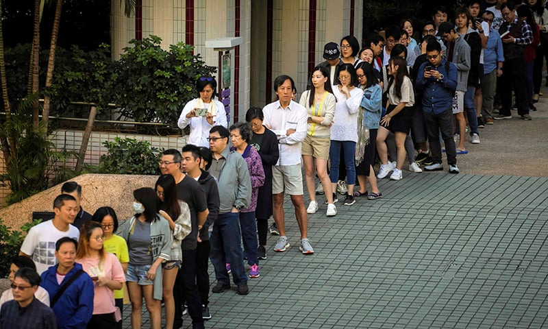 People queue to cast their vote during the district council elections in South Horizons in Hong Kong on Sunday. — AFP