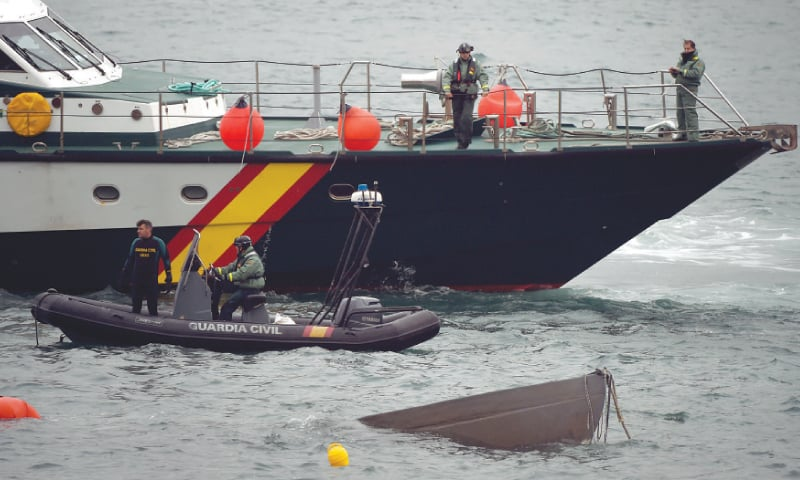 The prow of a submarine used to transport drugs illegally emerges as Spanish police divers work to refloat it.—AFP