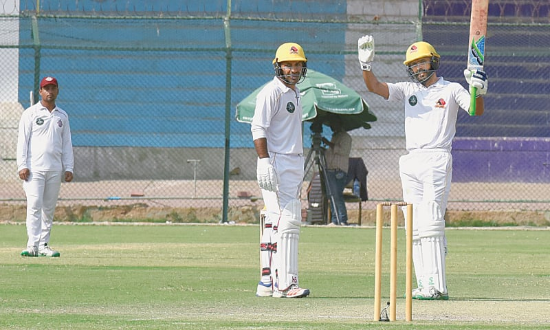 KARACHI: Fawad Alam celebrates another milestone on his way to reaching the double century as Sindh skipper Sarfraz Ahmed looks on during the Quaid-e-Azam Trophy match against Southern Punjab at the National Stadium on Wednesday.—Tahir Jamal/White Star