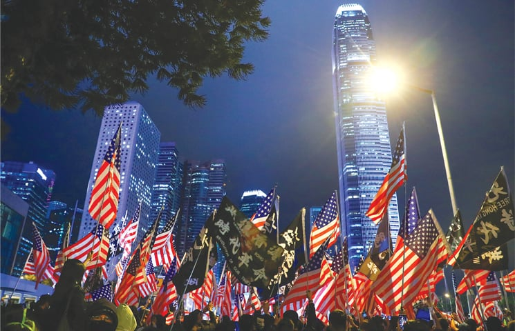 HONG KONG: Thousands of activists hold American flags on Thursday night at a Thanksgiving Day rally to thank the US for passing the bills.—Reuters