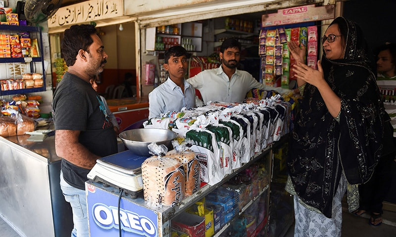 In this picture taken on October 16, transgender beautician Bebo Haider (R) speaks with a neighbouring shopkeeper Mohammad Akram (L) in Karachi.  — AFP
