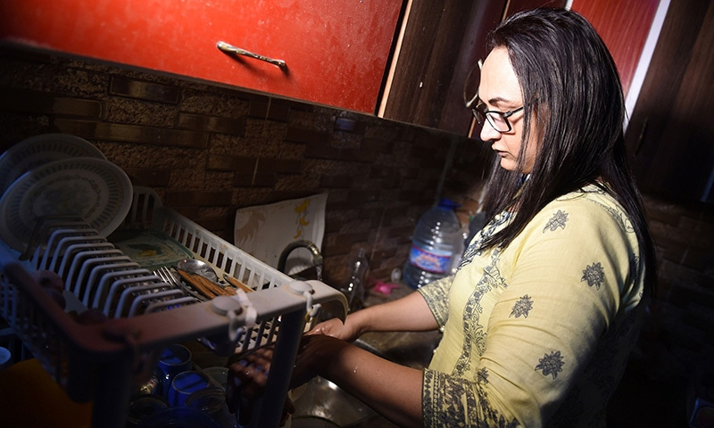 In this picture taken on October 16, transgender beautician Bebo Haider cleans dishes in her home in Karachi. — AFP