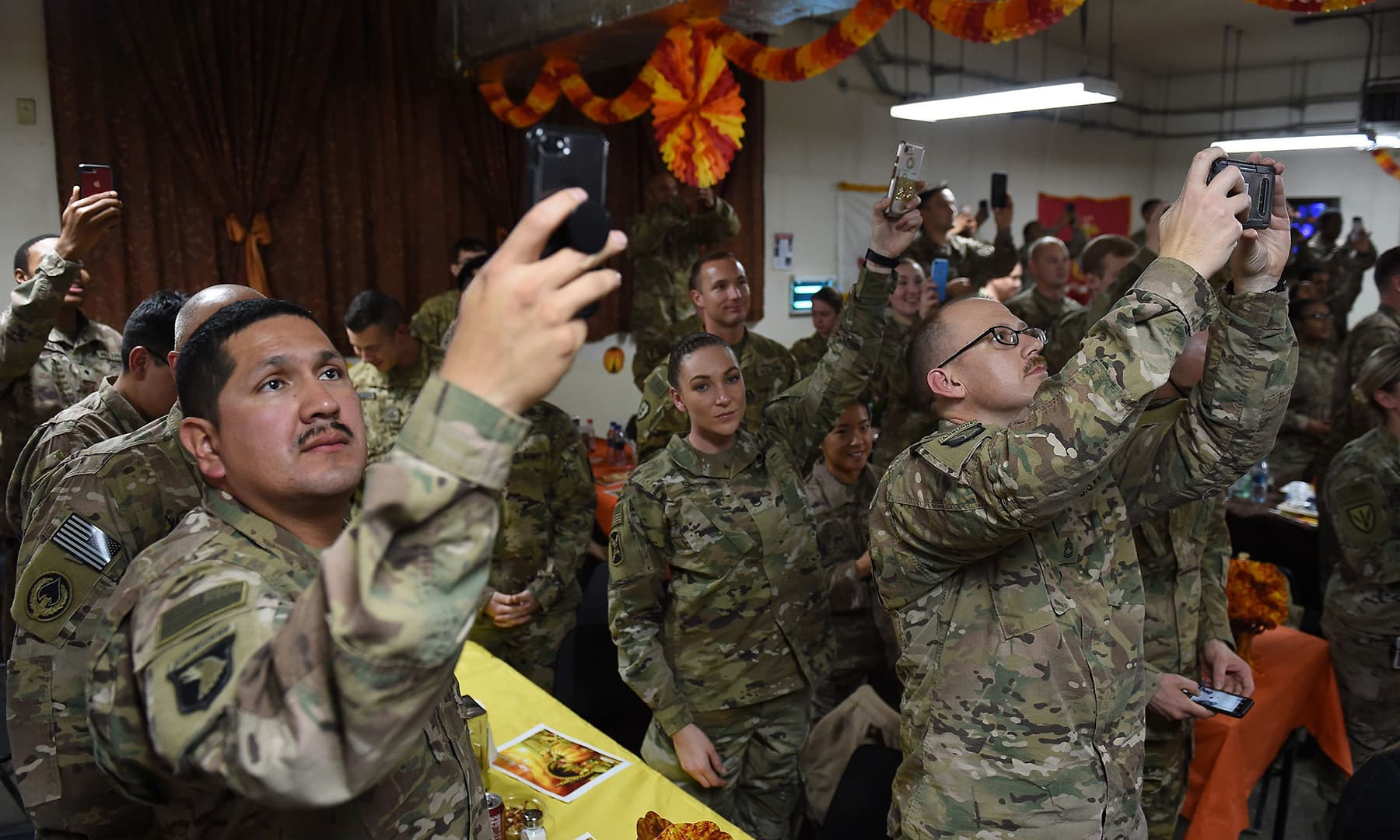 Soldiers take pictures of US President Donald Trump (unseen) during a Thanksgiving dinner to US troops at Bagram Air Field during a surprise visit on November 28 in Afghanistan. — AFP